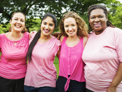 Group of women in pink smiling.