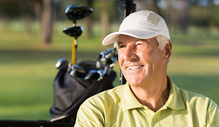 Male golfer looking off smiling.